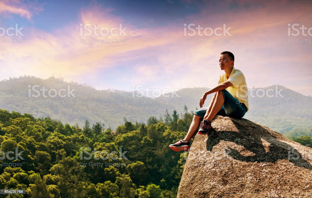 Asian man sitting on ledge stock photo