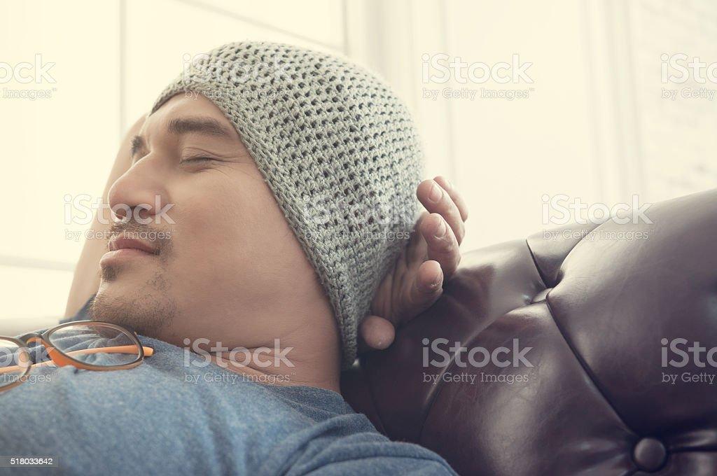 Asian man sleep on a brown sofa stock photo