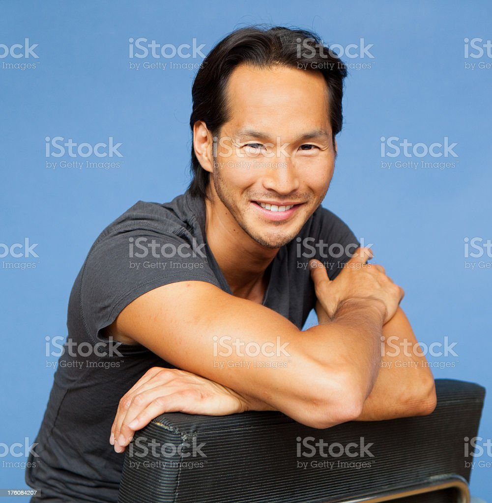 asian man smiling sitting on chair back to front royalty-free stock photo