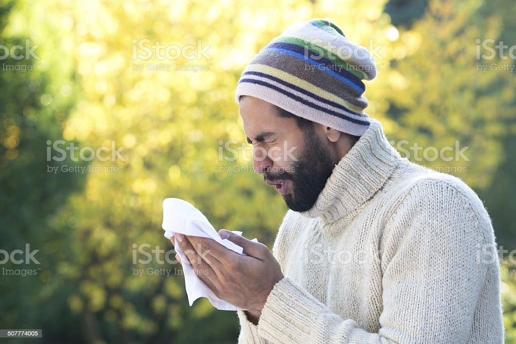 Asian Man Sneezing into Tissue stock photo