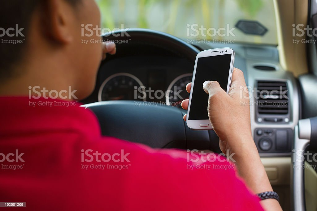 Asian man texting while driving stock photo