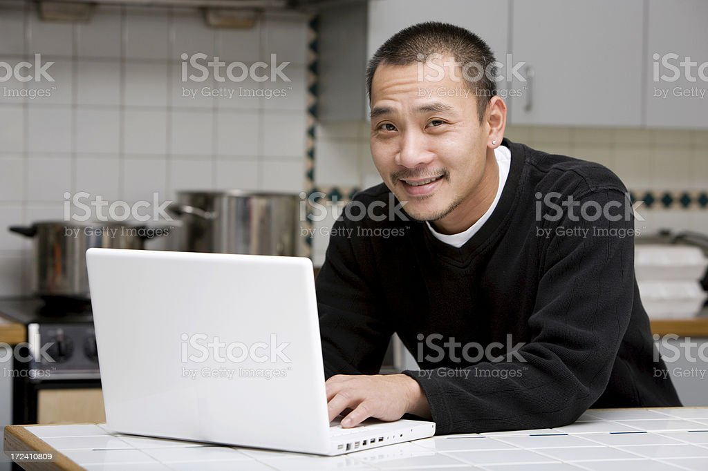 Asian Man Using Laptop in Home Kitchen, Copy Space royalty-free stock photo