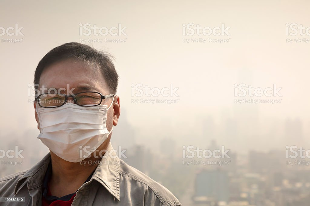 Asian man wearing mouth mask against air pollution stock photo