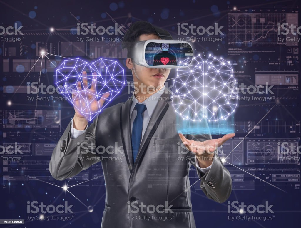 Asian Man wearing virtual reality in action hand holding the line of hearth shape and brain over the digital virtual display background, VR technology concept stock photo