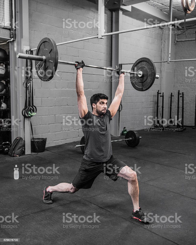 Asian man with barbell raised above his head in cross stock photo