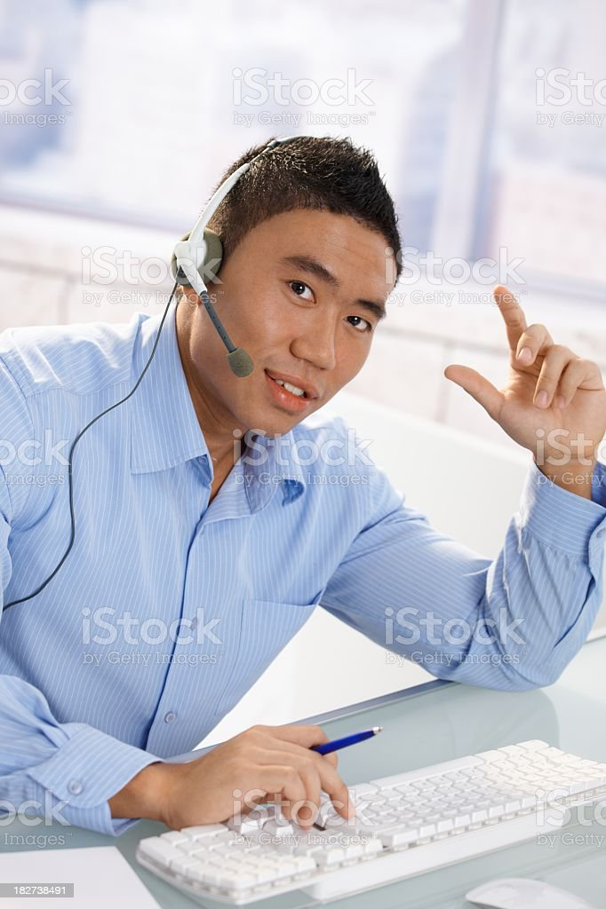 Asian man with headset at office desk royalty-free stock photo