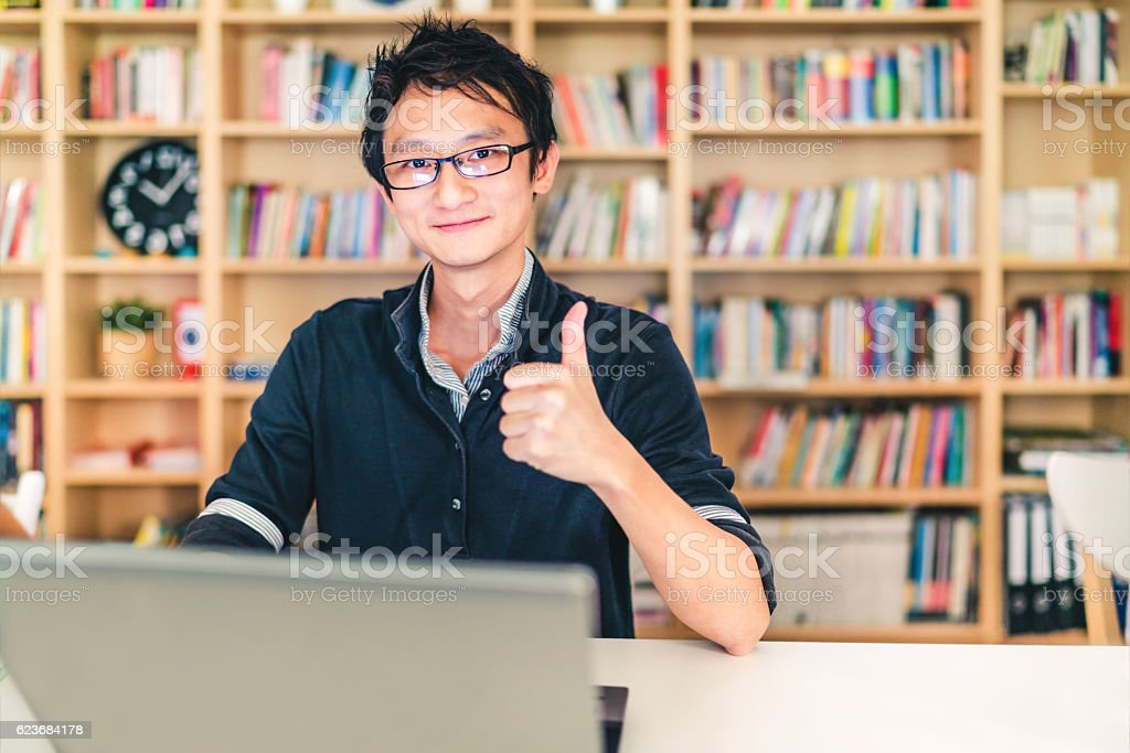 Asian man with laptop, thumbs up, at home office, library stock photo