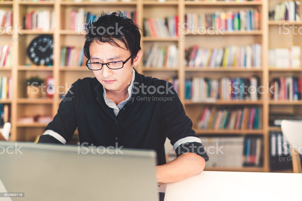 Asian man working on laptop with serious face stock photo