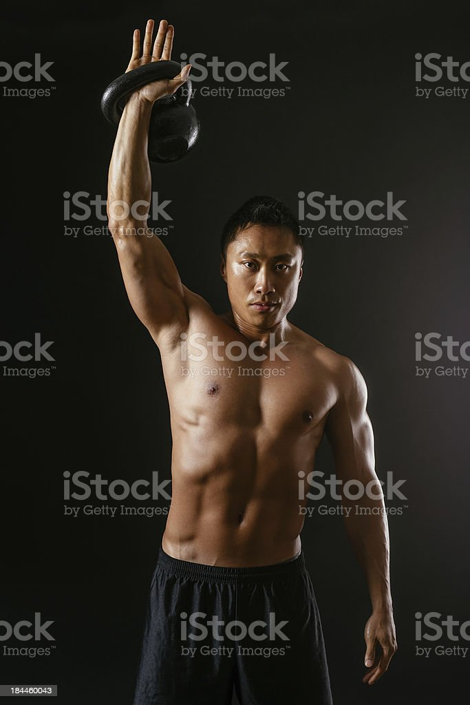 Asian man working out with kettle bell royalty-free stock photo