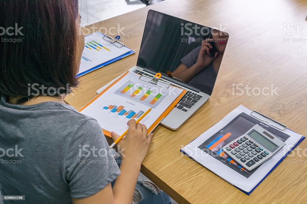 Asian manager checking sales reports in her business office stock photo