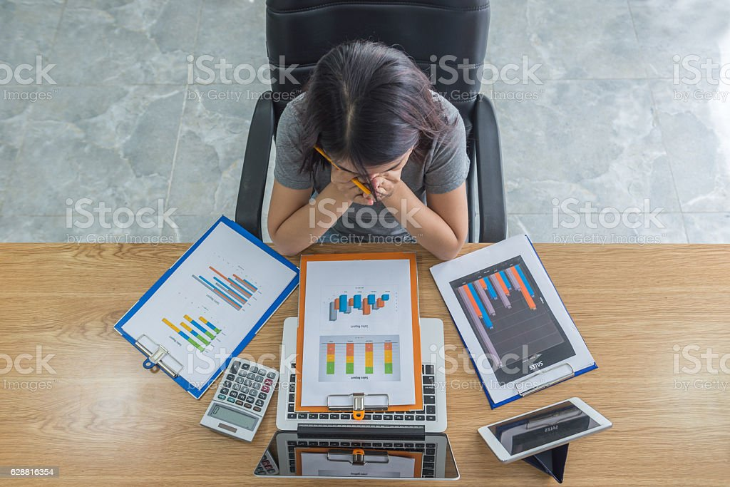 Asian manager exhausted and frustrated after checking many sales reports stock photo