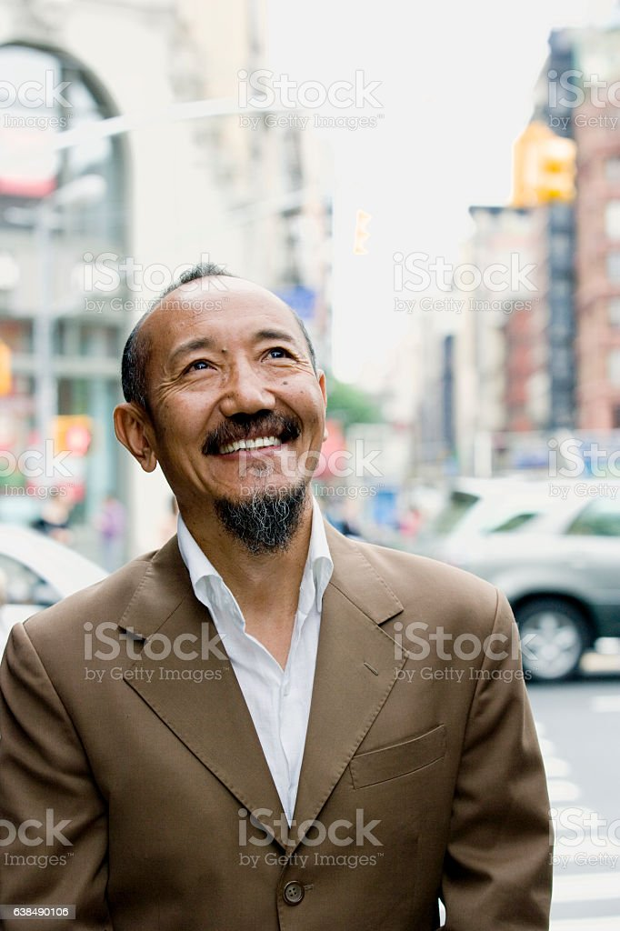 Asian mature man looking upward in downtown city stock photo