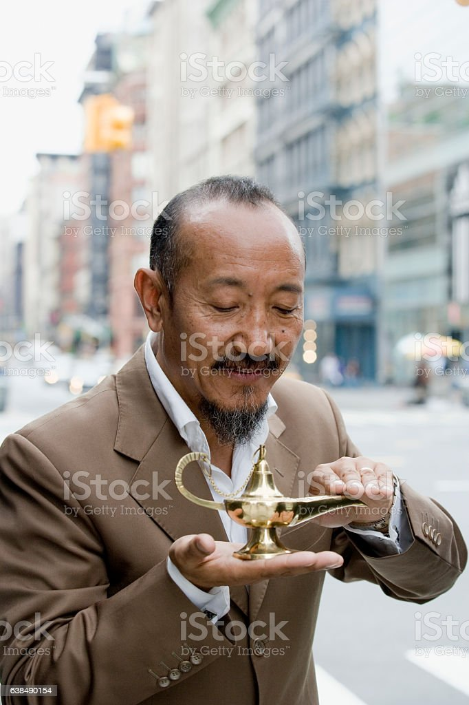 Asian mature man rubbing genie lamp in downtown city stock photo