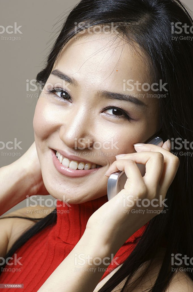 Asian model smiling on the phone royalty-free stock photo