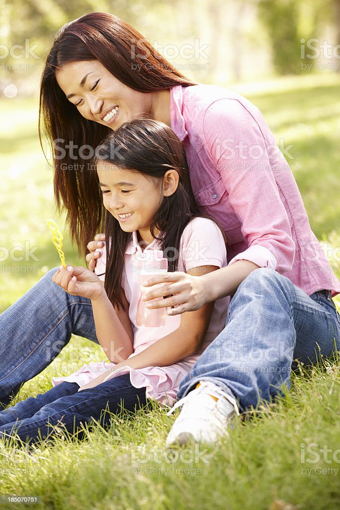 Asian mother and daughter blowing bubbles in park royalty-free stock photo