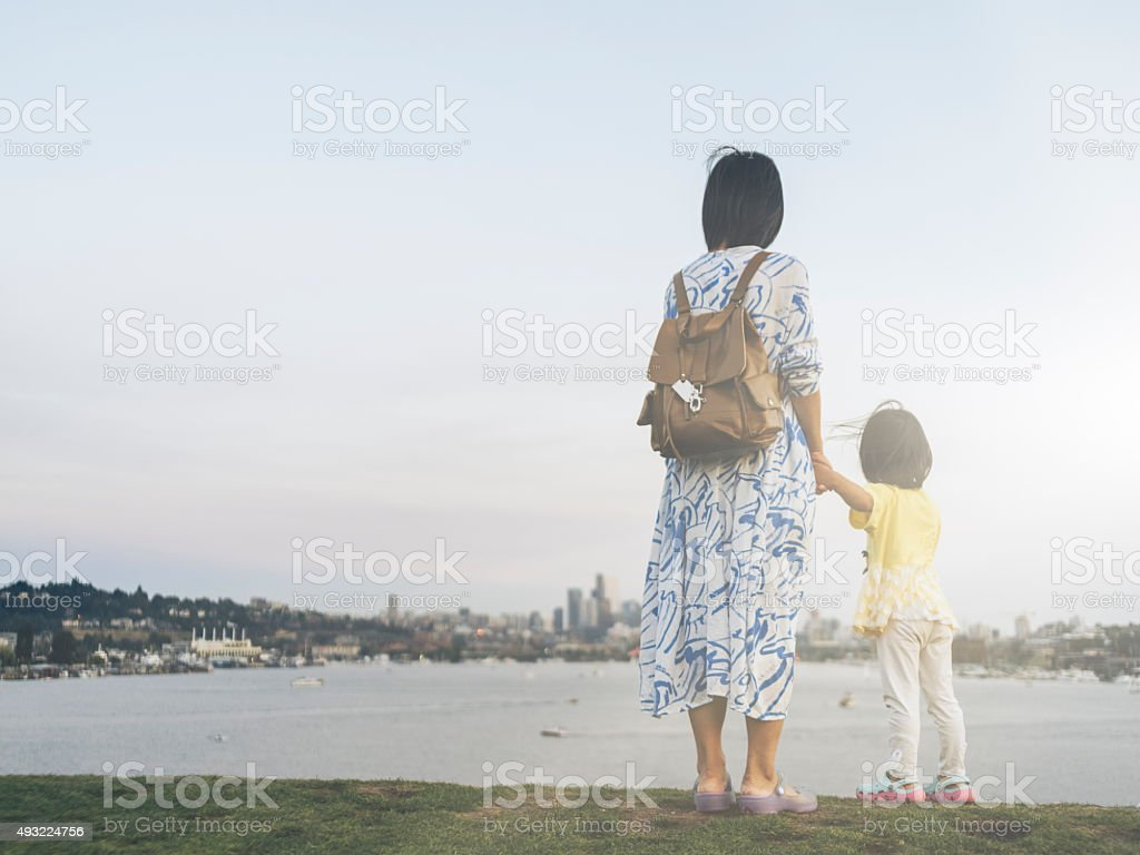asian mother and daughter looking at skyline of seattle stock photo