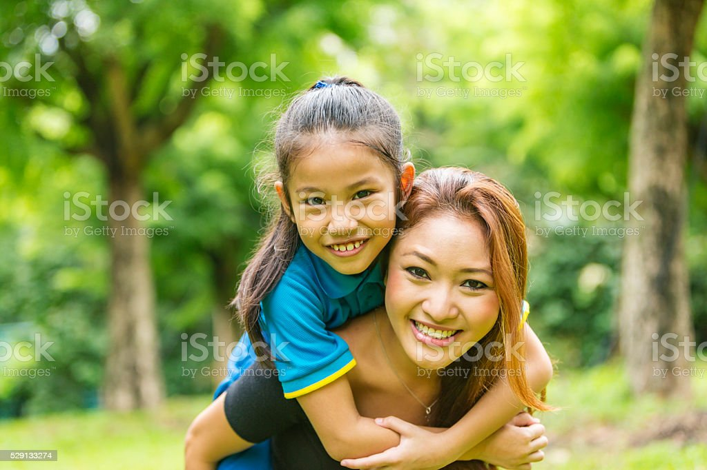 Asian Mother and Daughter Piggybacking Together in the Park stock photo