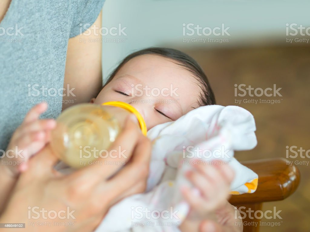 Asian mother feeding bottle her baby. royalty-free stock photo