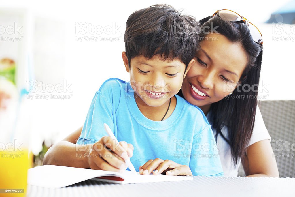 Asian mother helping her son with his homework stock photo