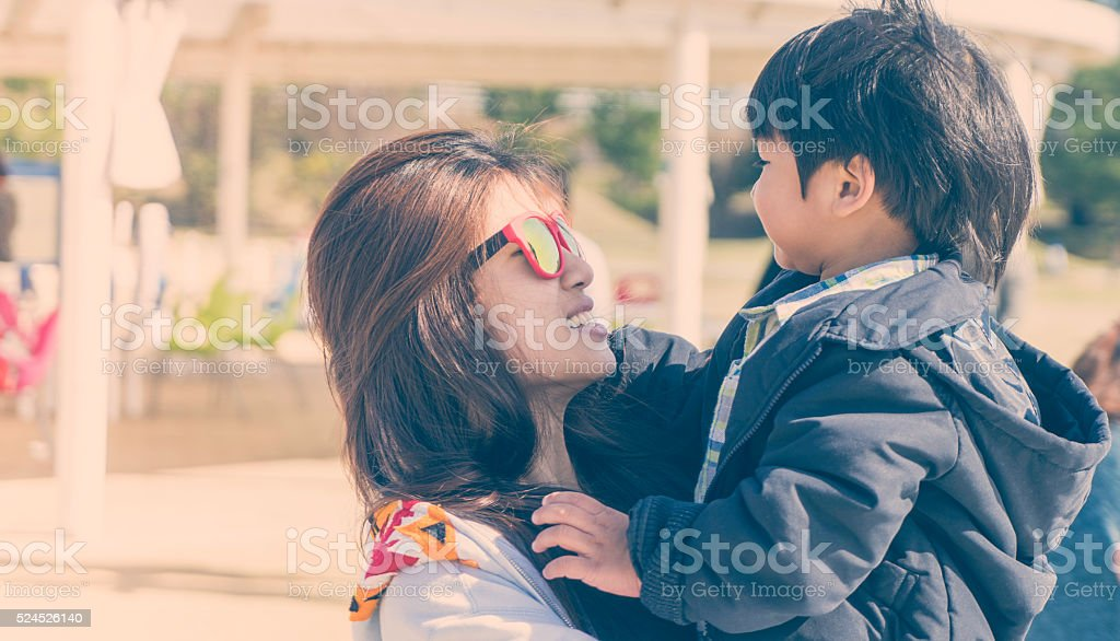 Asian Mother holding her son high up in vintage tone stock photo