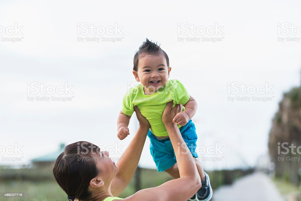 Asian mother lifting 11 month old baby boy stock photo