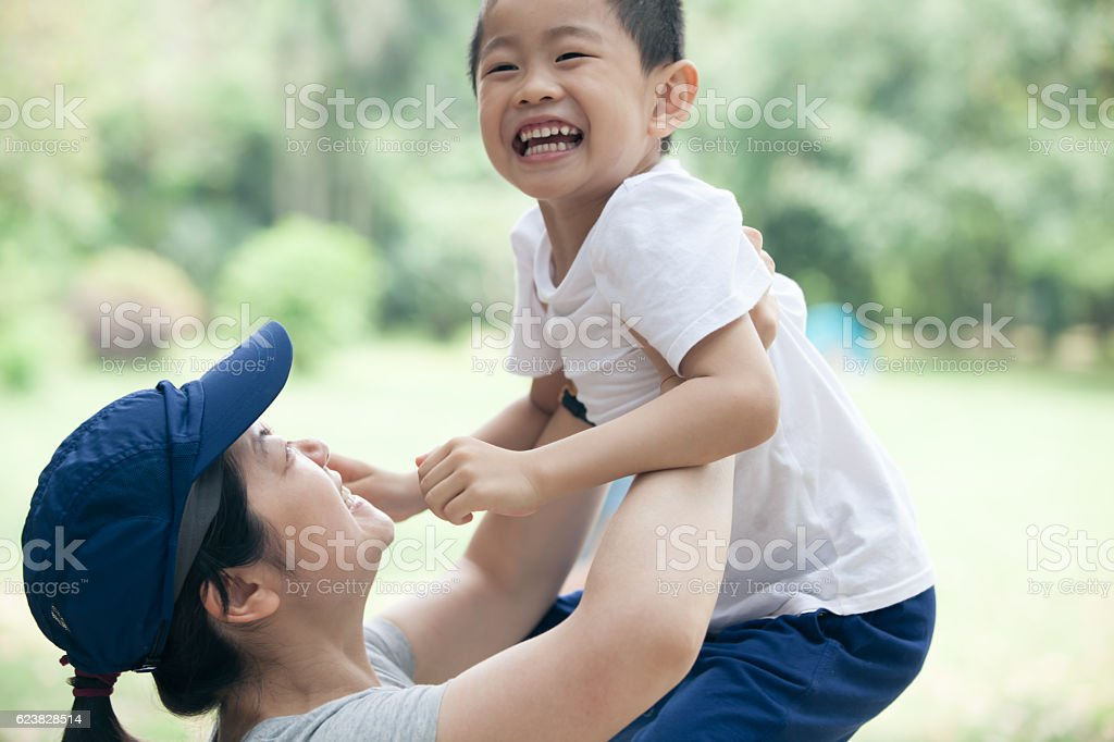 Asian mother lifting son happily oudoors stock photo