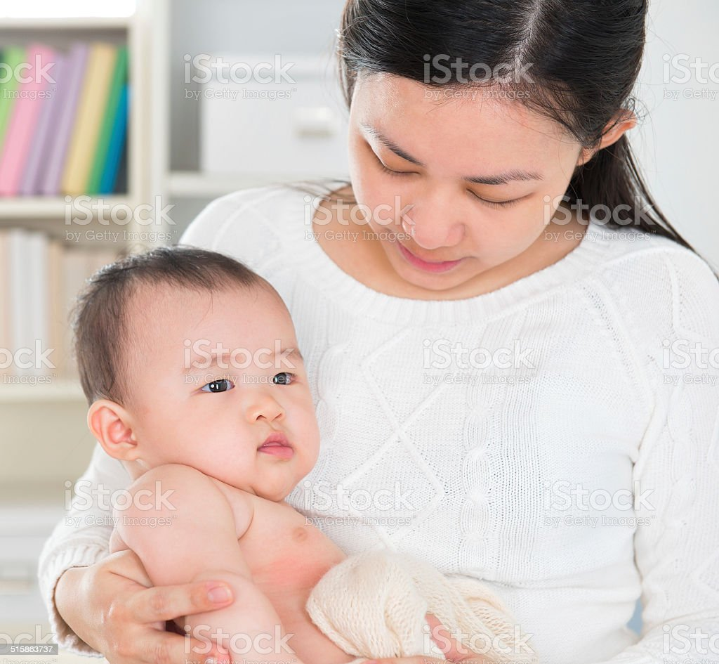 Asian mother pampering baby girl stock photo