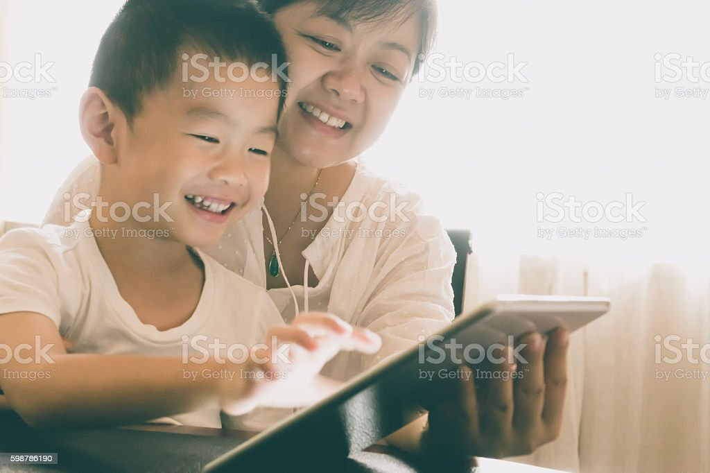 Asian mother teach son with digital tablet indoors stock photo