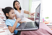 Asian mother teaching to littler girl to use laptop computer