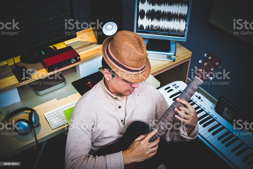 asian musician playing acoustic guitar in recording studio stock photo