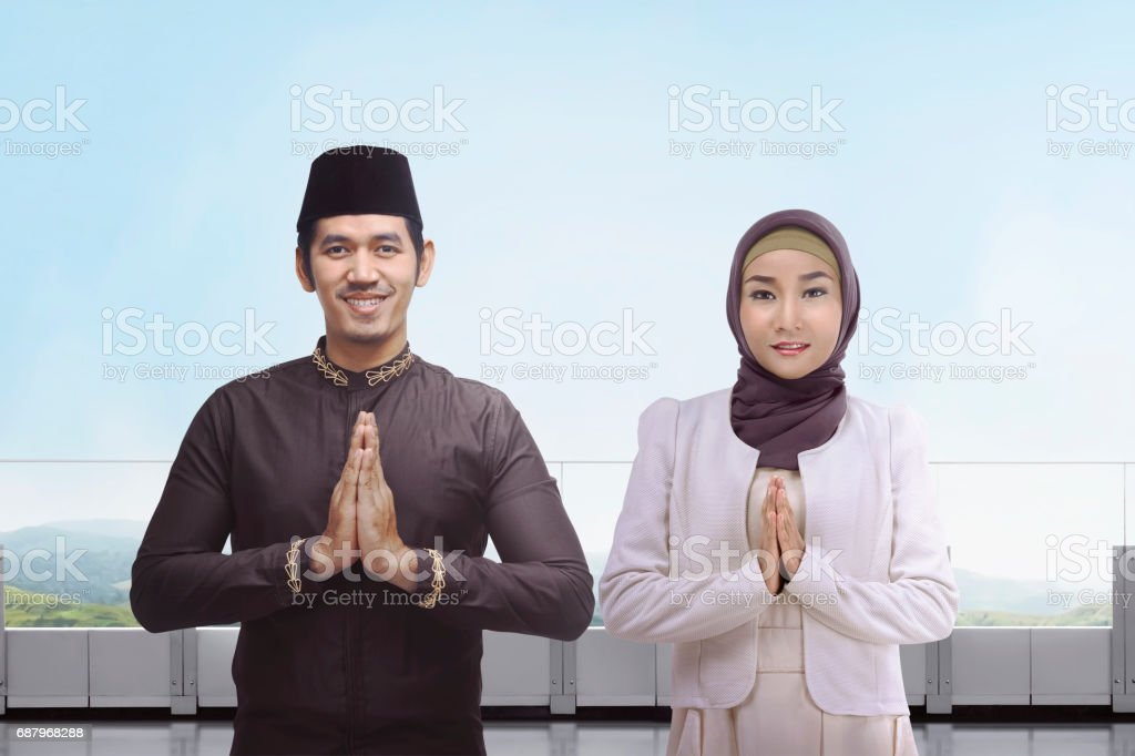 Asian muslim man and woman with traditional dress praying together stock photo