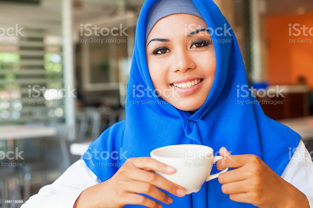 asian muslim woman enjoing a cup of tea stock photo