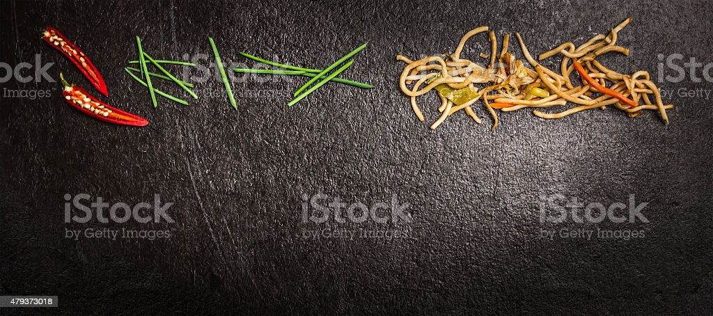 Asian noodles with chives and chili on dark slate background stock photo