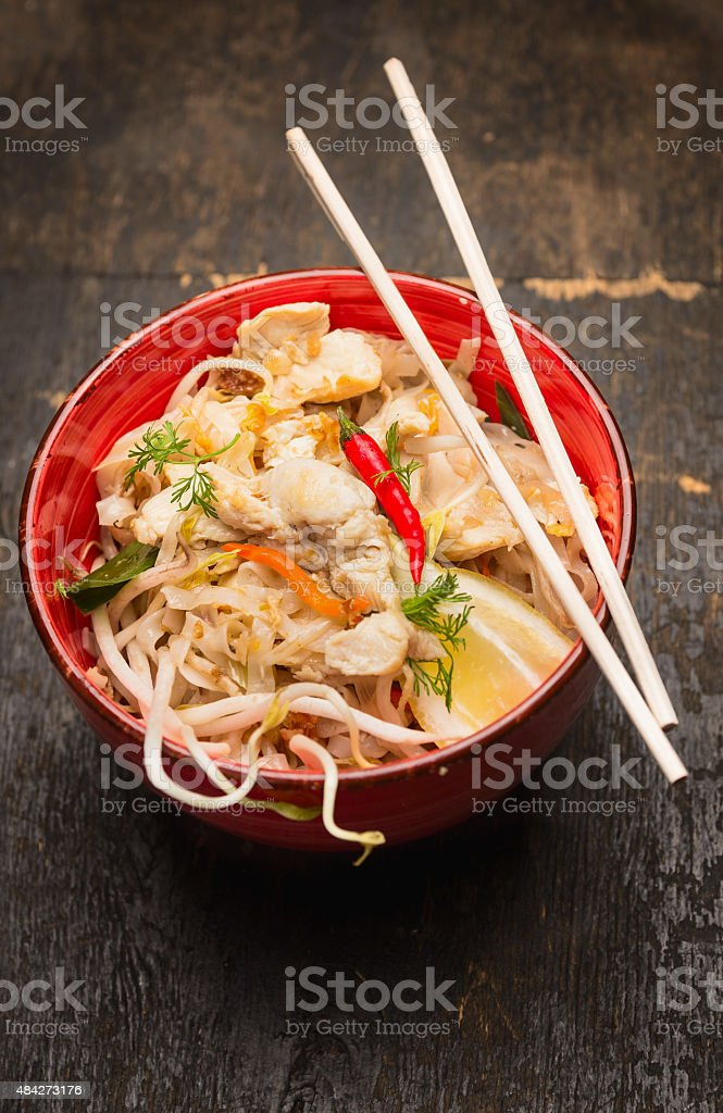 Asian noodles with chopstick, chicken and sprouts in red bowl stock photo