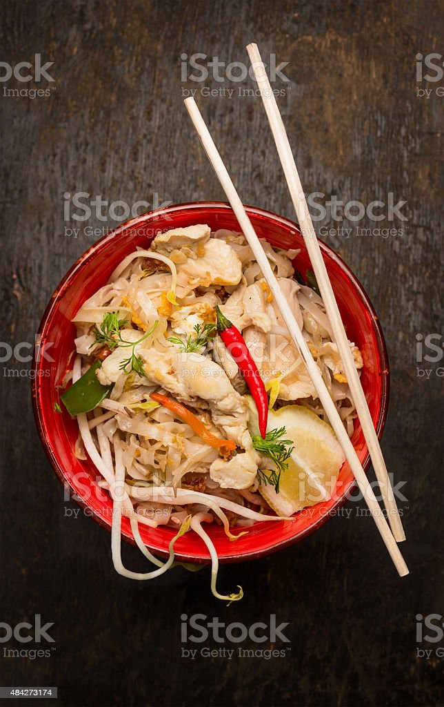 Asian noodles with chopstick, chicken and sprouts on wooden background stock photo