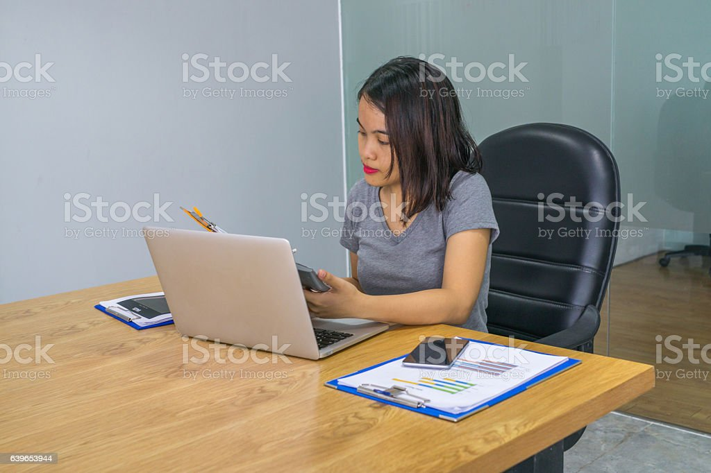 Asian office lady working on sales report at office alone stock photo