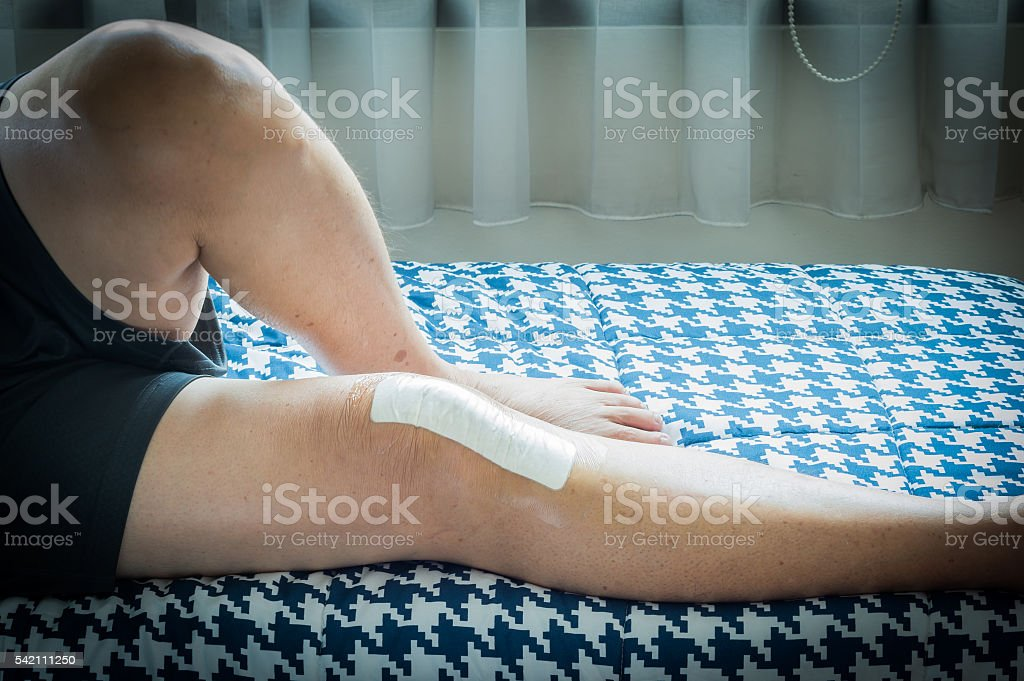 Asian old man with plaster on his knee stock photo
