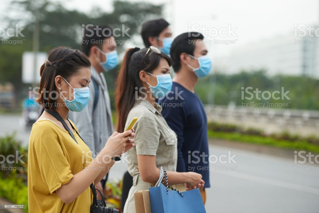 Asian pedestrians in protective masks stock photo
