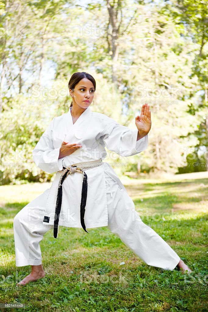 A shot of an asian woman practicing karate