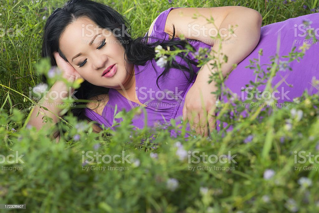 Asian pregnant woman laying on grass royalty-free stock photo