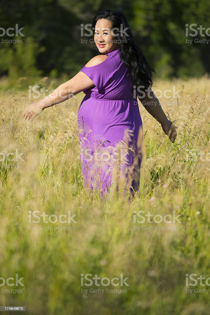 Asian pregnant woman walking in grass field royalty-free stock photo