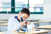 asian primary student does experiment by using microscope in classroom