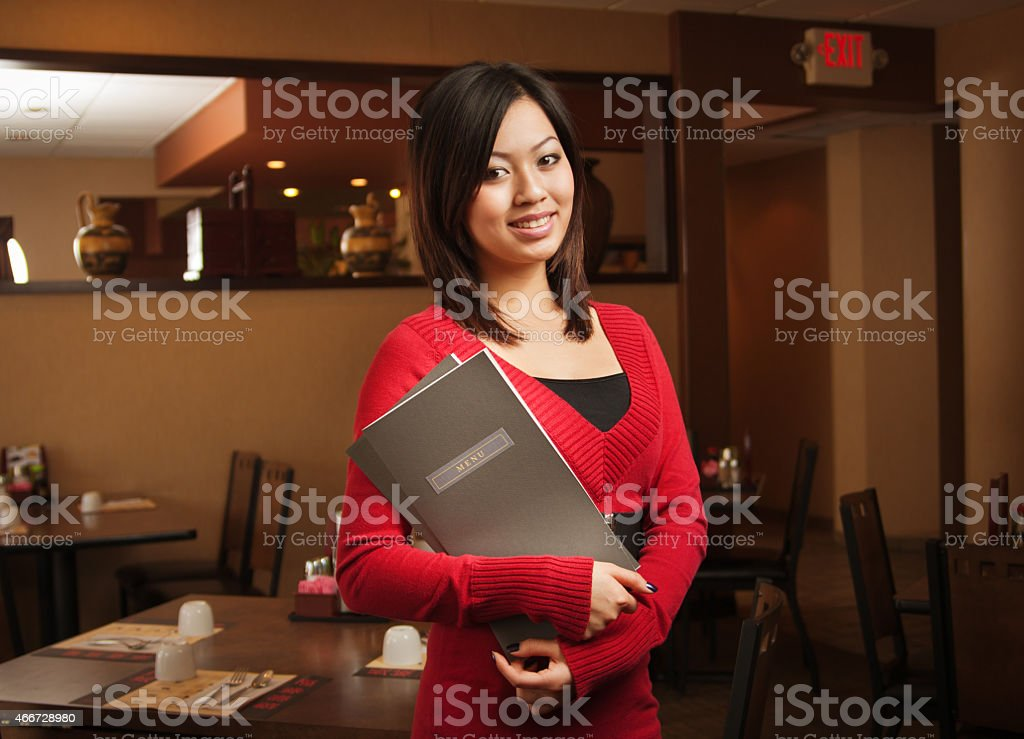 Asian Restaurant Greeting Host or Business Owner Holding Menu, Smiling stock photo