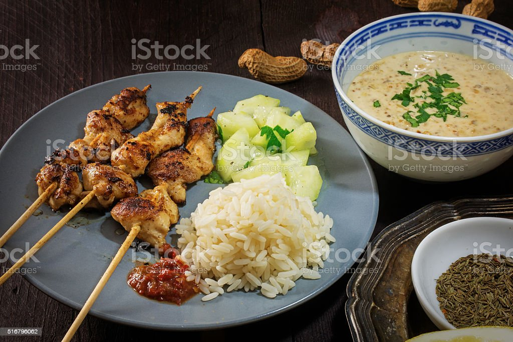Asian satay meat skewers with cucumber salad and peanut sauce stock photo