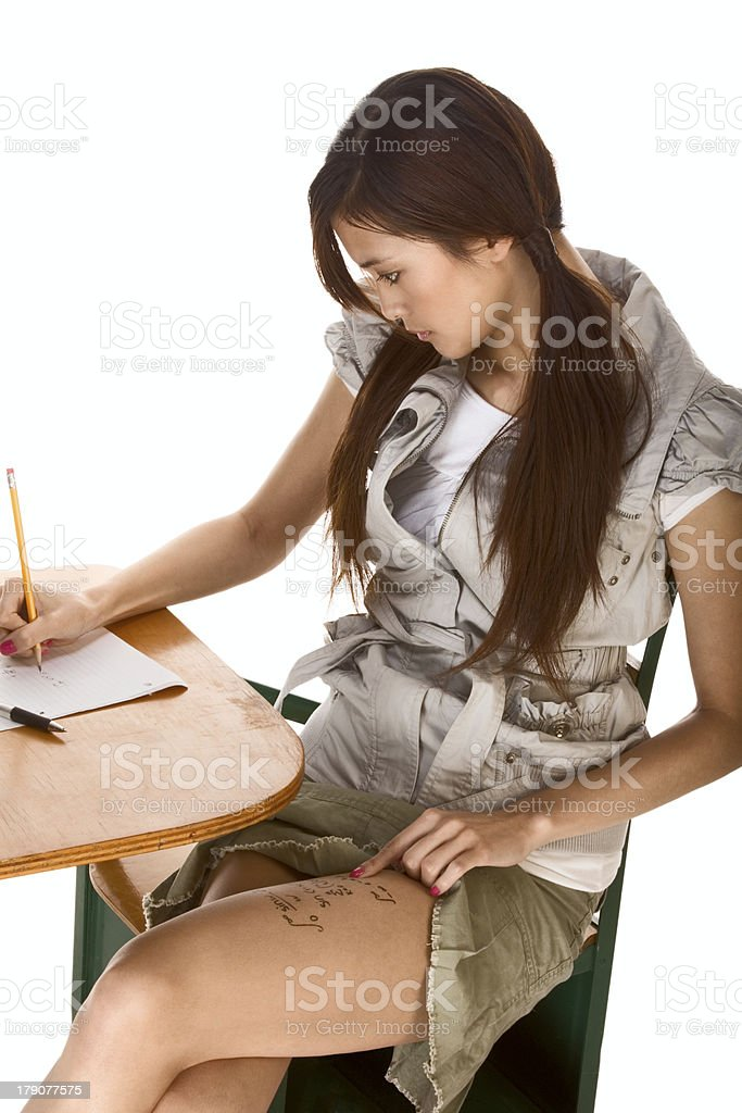 Asian schoolgirl is preparing to cheat on test royalty-free stock photo