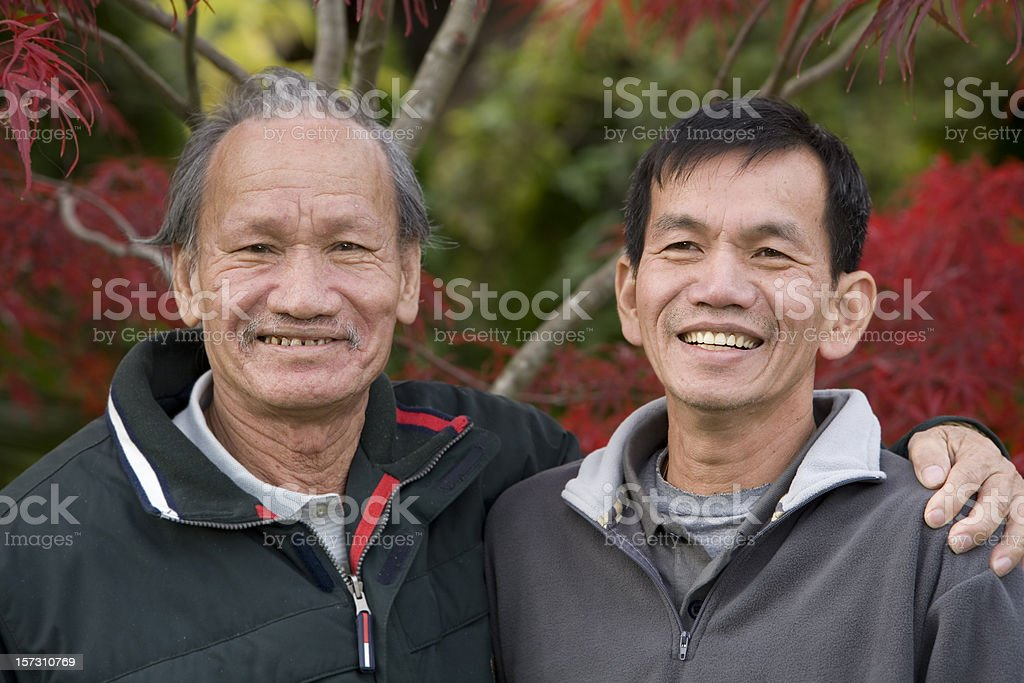 Asian Senior and Adult Male Relatives Embracing for Portrait Outdoors royalty-free stock photo
