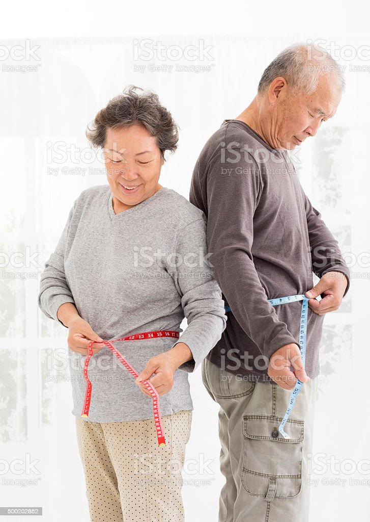 asian senior couple measuring  belly with measurement tape stock photo