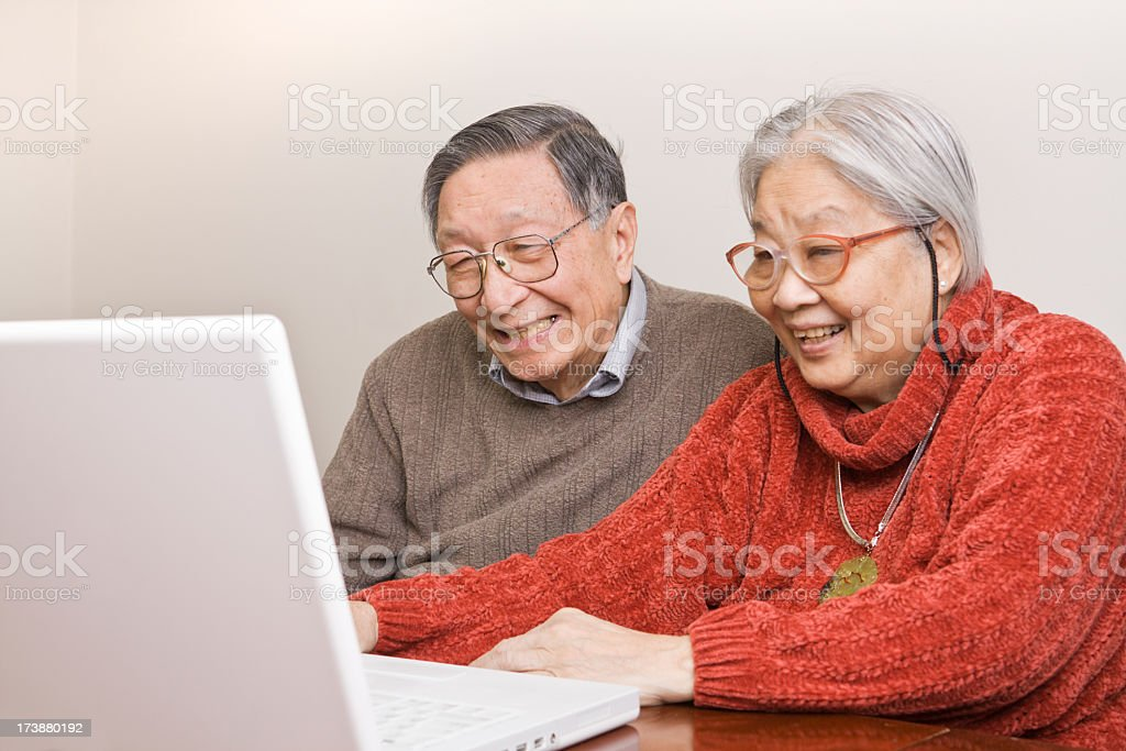 Asian Senior Couple, Retired Chinese Grandparents Using Laptop Computer Together royalty-free stock photo