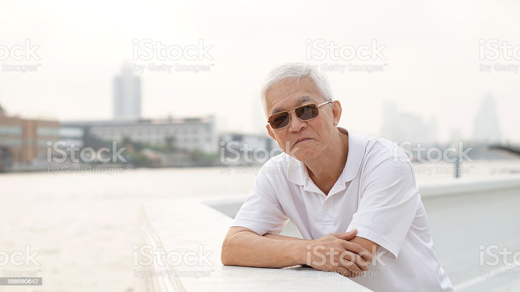 asian senior man stand relax next to river wearing sunglasses stock photo
