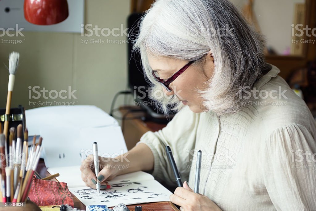 Asian senior woman artist sketching stock photo